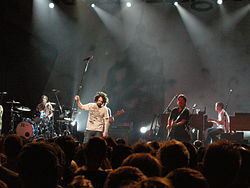 Counting Crows in Brussels, 2008. L to R: Bogios, Duritz, Immerglück, and Gillingham. Vickrey is cut off at the left, Powers is behind Duritz, and Bryson is out of frame.
