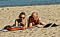 Couple reading at the beach (36294639151).jpg