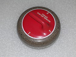 The curling stone or rock is made out of granite.