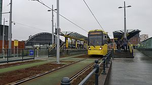 Deansgate-Castlefield tram stop - Trams at Deansgate-Castlefield tram stop in 2017, with the Manchester Central complex in the background.