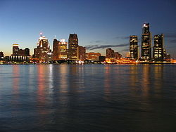 Tall buildings with city lights at dusk, reflected over still dark water