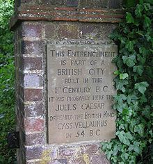 A commemorative plaque in a brick pillar surrounded by woods