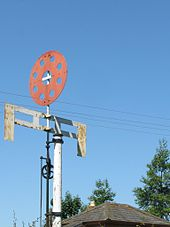 A white pole supports two cross-arms joined by four short verticals to make a grid. Above that is a red disc perforated by eight holes.