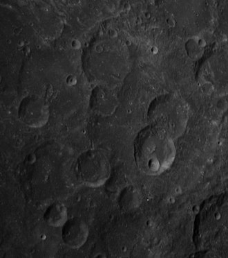 Dreyer (crater) - Oblique Apollo 14 Hasselblad camera image Dreyer and Ginzel and several of their satellite craters.  From center, Ginzel is at approximately 12:00, and Dreyer is at approximately 8:00. The small crater at 9:00 is Dreyer W.  Dreyer C is just east of Dreyer, and Dreyer K and J are to the south and southeast of Dreyer.