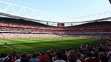 Vue depuis la tribune basse d'un grand stade avec ses tribunes remplies avec un match en cours.