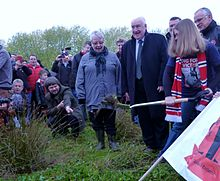 A group of people stand in a grassy field in daylight watching a woman digging the ground using a spade. People are taking pictures of the event and have brought banners and football scarves.