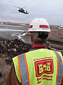 FEMA - 40767 - USACE worker watches a helicopter drop sand bags in North Dakota.jpg