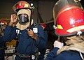 Flickr - Official U.S. Navy Imagery - A Sailor dons a firefighting helmet..jpg