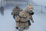 From right, U.S. Air Force Tech. Sgt. Jacy J. Vogelewede and Airman Rebecca M. Hanson, both of the 119th Aircraft Maintenance Squadron, make their way through harsh winds and snow in their chemical warfare gear 080209-F-WA217-037.jpg