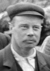 Fuzzy head-and-shoulders photo of a 40-year-old man in a cloth cap and mustache