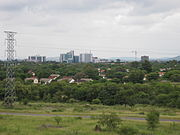 A skyline picture of Gaborone with a field, forest, and low-lying houses in the foreground and buildings along the horizon.