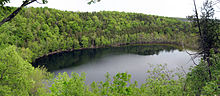 A small lake seen from the top of the cliffs surrounding it. There are trees growing on the steep slopes; their leaves are light green.