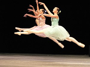 Three ballet dancers performing a grand jeté jump