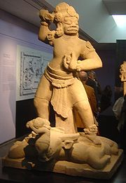 This statue of a dvarapala (temple guardian) was stationed in an entry hallway or gopura of the Buddhist monastery at Indrapura.  The guardian treads on a bull, who in turn disgorges a small warrior, who in turn raises his sword against the guardian.