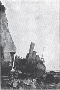 HMS Nubian, a destroyer, beached near cliffs with her bow blown off by a torpedo.