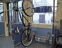 Bike hanging sideways on a rack inside a train