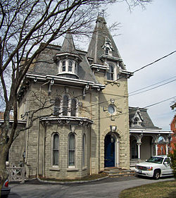 An ornate grayish-brown house with peaked and pointed towers with a bare tree at the left and a white car in a driveway on the right in front of it.