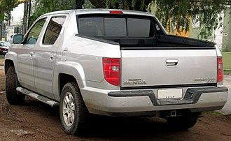 Honda Ridgeline - Left-rear quarter of the Gen1 Ridgeline—note the sloping C-pillar, roof garnish design, and tailgate height—(2011 Chilean RTL with OEM accessory side-steps and back-up sensors)