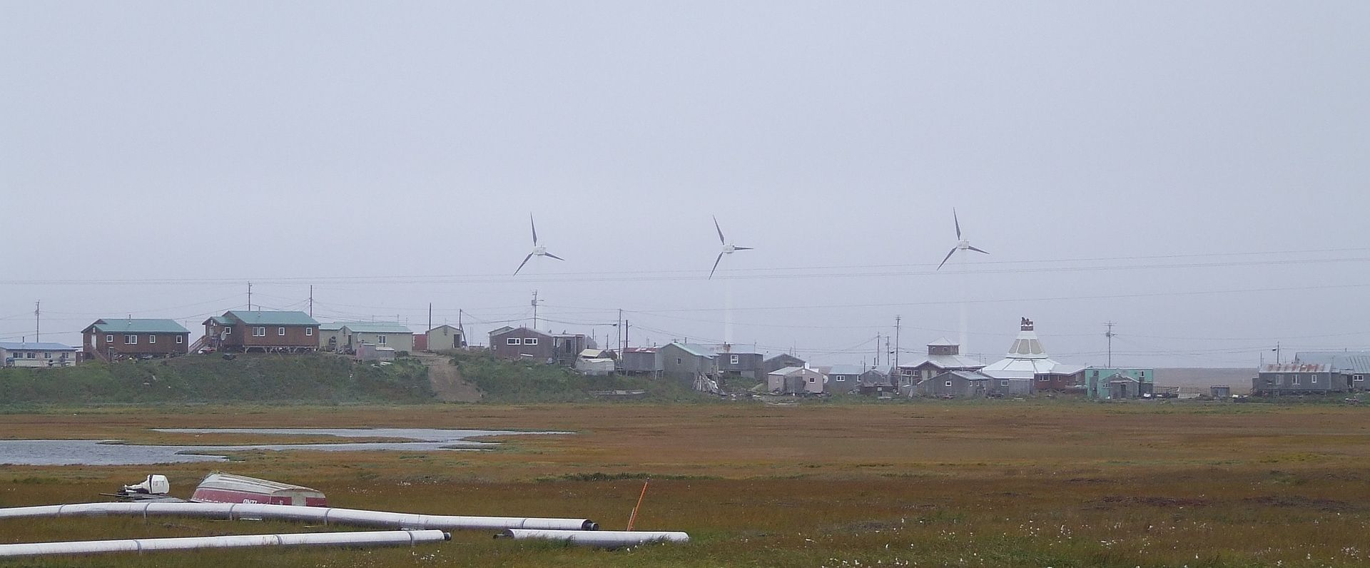Hooper Bay with wind turbines in background.