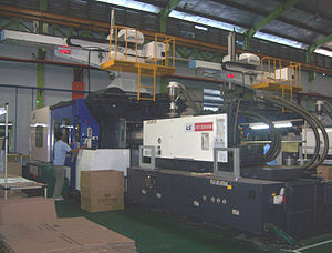 Injection molding machine - A 1300-ton injection molding machine with robotic arm