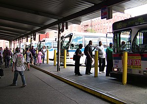 165th Street Bus Terminal - Passengers board buses at the terminal.