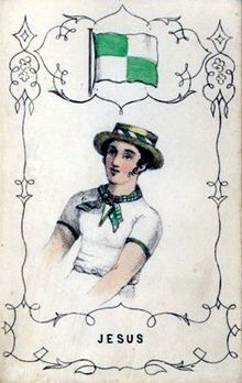A man wearing a green and white neckerchief and a straw boater, under a green and white flag
