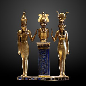 Gold statuette of three human figures. On the right is a woman with a horned headdress, in the center is a squatting man with a tall crown on a pedestal, and on the left is a man with the head of a falcon.