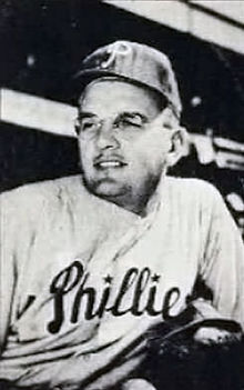 "A black-and-white image of a man in a white pinstriped baseball uniform with ""Phillies"" across the chest, a dark baseball cap with a white ""P"" on the front, and round glasses"