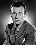 Black and white photo of John Wayne in 1940--a white man with a broad forehead, dark straight hair and dark eyes, wearing an elegant suit, around 34 years of age.