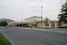 The main terminal building of an airport, with a road and parking lot situated near the building.