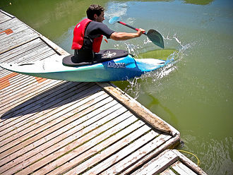 Confluence Outdoor - A kayaker in a Dagger kayak launches into flat water