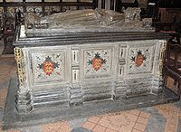 A photograph of the tomb of King John; a large carved, square, stone block supports a carved effigy of the king lying down.