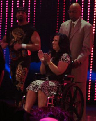 La Familia (professional wrestling) - Vickie Guerrero spent much of her time in a wheelchair. She is seen here being pushed by Teddy Long and accompanied by nephew, Chavo Guerrero.