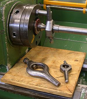 Lathe center - Dead center (the conical piece) mounted in the spindle of a lathe and being used to support a workpiece being driven by a carrier setup
