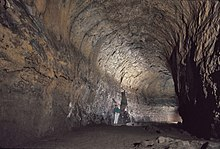 A hiker stands under the arched ceilings of the Lava River Cave, which was formed from a lava flow at Newberry Volcano