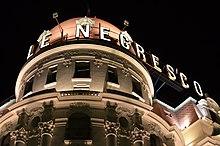 Vue en contre-plongée de nuit du haut d'un palais sur lequel on voit en majuscules électrifiées «Le Negresco».