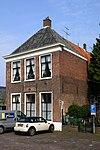 foto van Vrijstaand woonhuis, waarschijnlijk vroeger behorende bij het Pesthuis. Voorste gedeelte met tentdak, achterste gedeelte even hoog, doch met zadeldak. Houten deuromlijsting