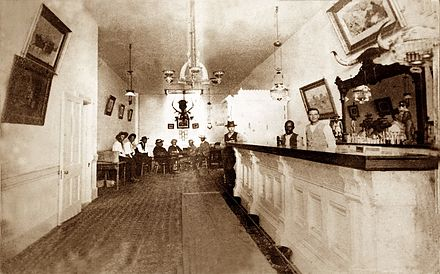 Photo of the interior of the Long Branch Saloon in Dodge City, Kansas, taken between 1870 and 1885 Long Branch Saloon interior.jpg