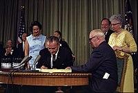Lyndon Johnson signing Medicare bill, with Harry Truman, July 30, 1965.jpg