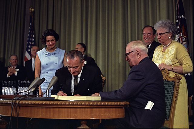 Photo: President Lyndon B. Johnson signs the Medicare Bill, with President Harry S. Truman seated next to him. Others looking on include Lady Bird Johnson, Vice President Hubert Humphrey, and Bess Truman.
