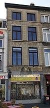 foto van Huis met gepleisterde lijstgevel, met vensters in hardsteen op horizontale reliefbanden. Gevelsteen met een distilleerketel
