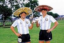 Photographie en couleurs. Diego Maradona et Daniel Passarella posent en tenue de football argentine et avec un chapeau mexicain, un verre à la main, tout sourire.