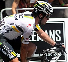 A road racing cyclist wearing a black and white jersey with yellow and green trim. His bicycle is only partly visible.