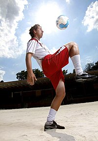 A man standing on one leg, with the knee of his other leg raised to waist height. A ball can be seen in midair, roughly 50cm above his knee.