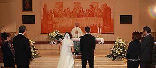 Cerimonia di nozze cattolica. Al centro, gli sposi e il sacerdote, ai lati, i testimoni degli sposi