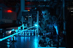 A military scientist operates a laser on an optical table.