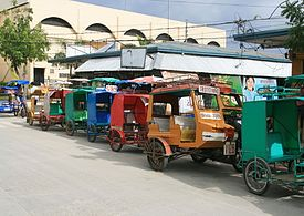 Trisikads (and one tricycle) for hire lined up outside public market in downtown Bantayan
