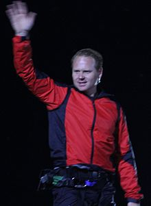 A man in a red jacket waves with his right hand raised high in the air