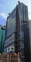 Ground-level view of a blue, glass, rectangular high-rise; attached to one side of the building are two structures consisting of poles that run the height of the building