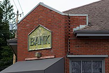 "A portion of a brick building, with an aged sign saying ""Bank""."